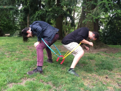 Two men stand back to back, crouching. They have hula hoops around their bodies, and attempt to pass a horseshoe from one hoop to the other.