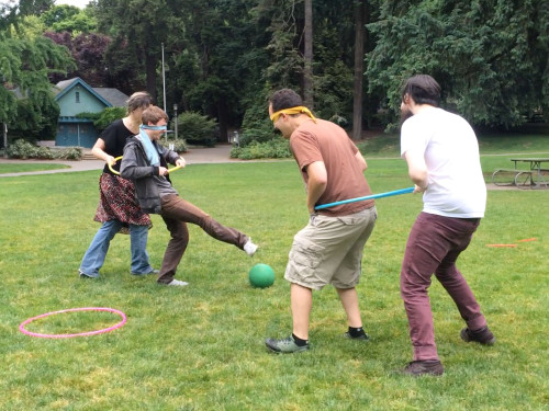 Marionette Soccer: four people on a grassy fiend. Two people are blindfolded. The other players use hula hoops to guide them toward a ball, which they attempt to kick.