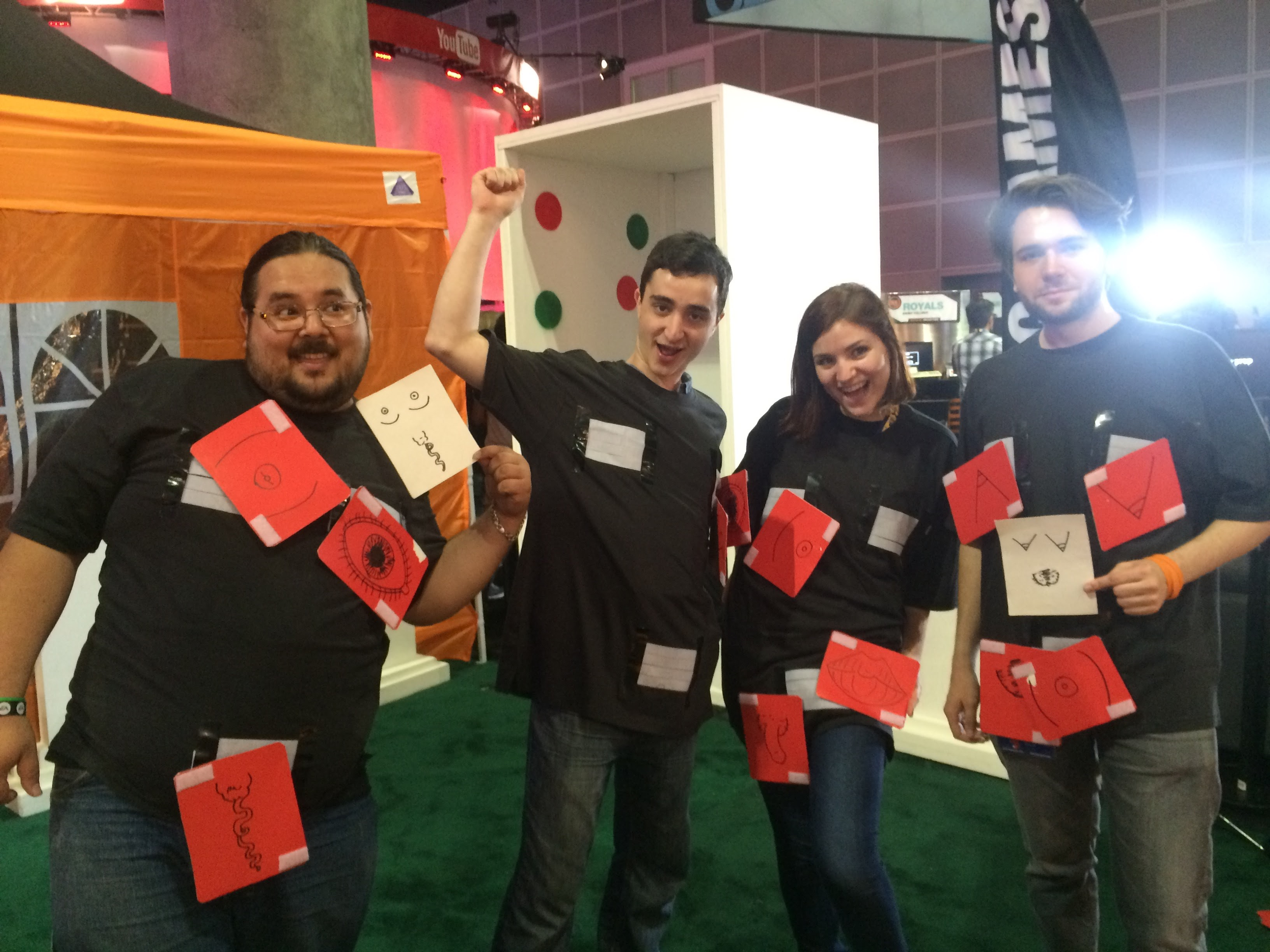 Four people stand together looking happy and triumphant. They are wearing black tee shirts with red cards attached with Velcro.