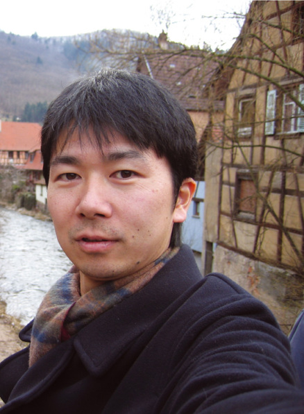A selfie of an Asian man with short hair, wearing a dark jacket and scarf. He's standing in front of a European village-style background, with a river and mountains visible.